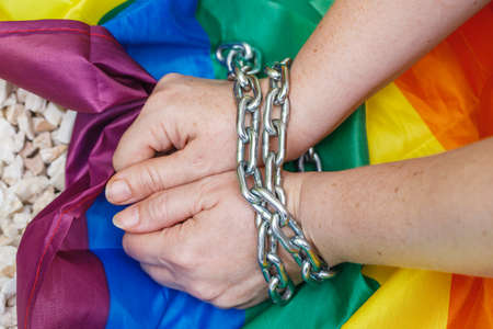 Female hands chained against the background of the LGBT flag. The concept of oppression an intolerance towards sexual minorities