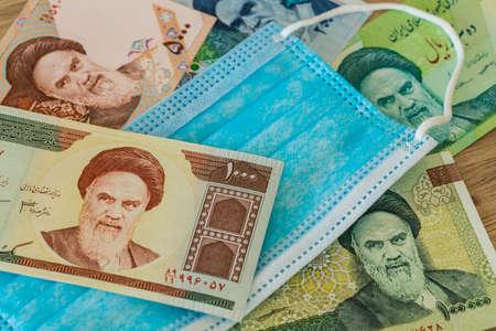 Iranian money, anti-virus mask. The concept of the country's economy during the coronavirus pandemic