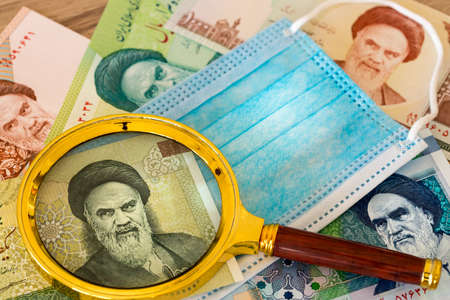 Iranian currency, Rials, anti-virus mask and magnifying glass. The concept of the country's economy during the coronavirus pandemic