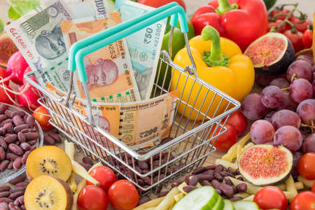 Shopping basket with Indian rupees money, around food products, vegetables and fruits. The concept of inflation, rising prices and more expensive food