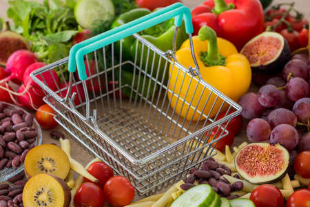 Empty shopping Cart. Lots of food, vegetables and fruits around. The concept of rising prices, inflation and more expensive food