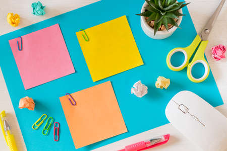 A large, blue card on the desk and three small colored sheets with space for text. Office and school accessories, computer mouse, pens, crumpled paper balls, scissors, mini flower in a pot, staples. 版權商用圖片