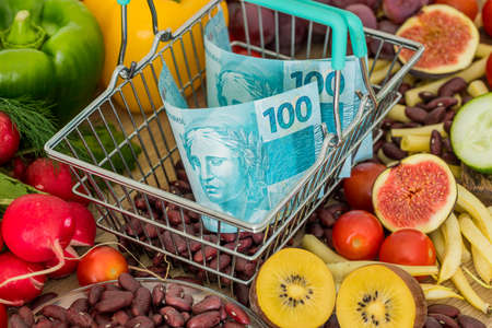 Shopping basket with Brazilian money, around food products, vegetables and fruits. The concept of inflation, rising prices and more expensive food
