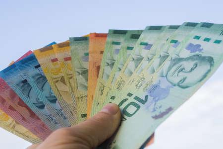 Costa Rica money held in hands against the sky