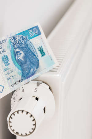 heating radiator and banknotes of 50 Polish zlotys. The concept of high costs of heating apartments