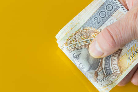 A bundle of Polish money, Two hundred zloty banknotes, Held in hands. Yellow background with place for text