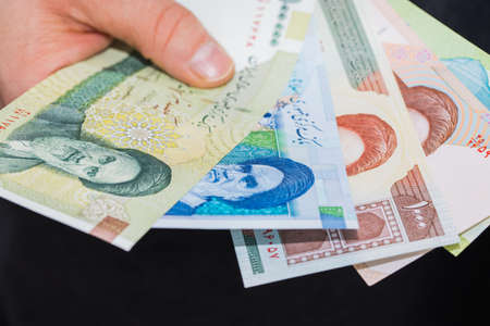 Iranian bills, Riyal, Assorted values, Money spread out and held in the hand