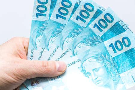 Brazilian Real. Money spread out in a fan, held in a man's hand
