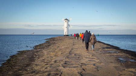 People walking towards the lighthouse in Swinoujscie in Poland, Winter