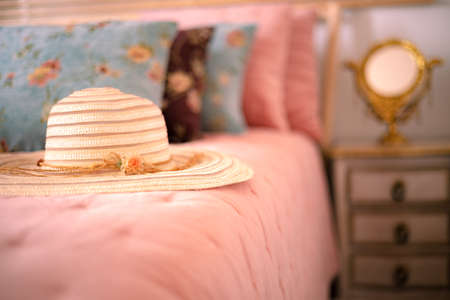 Stylish women sun hat lying on the bed next to the nightstand with a mirror. Elegance in a feminine style. Interior, Retro