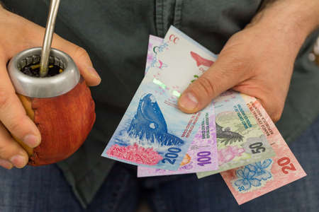 The man is holding Yerba mate and Argentinian money. Business and financial concept, Symbol of Argentina Foto de archivo