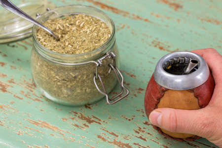 A hand holding a traditional Yerba mate vessel, next to a jar full of Paraguayan holly used to brew the drink