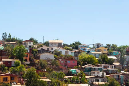 Bunch of houses on a hill in chile. Rudimentary and poor houses, colorful, between trees. 스톡 콘텐츠