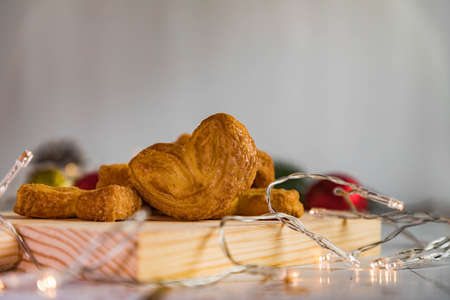 European pastries, palm cookie on wooden board and decorated Christmas tree. Luke, gift, red, gold and green balls. Tassels. Christmas background. Breakfast.