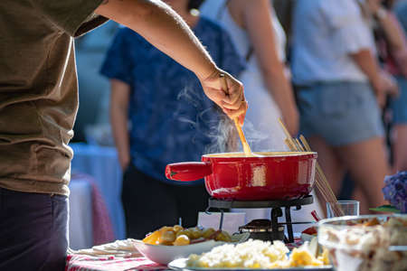 Close up detail shot of person's arm stirring a traditional tasty delicious pot of hot melted liquid swiss cheese fondue at an outdoor picnic in Switzerland blurred background bright colors copy space