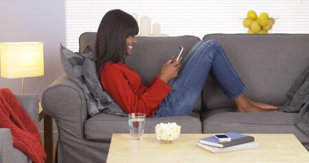 american content: Attractive black woman using tablet at home
