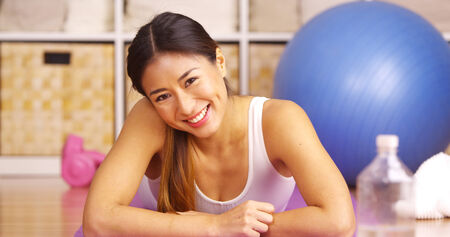 looking after: Happy Chinese woman lying on yoga matt Stock Photo