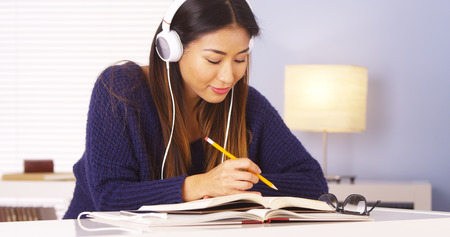 music book: Japanese woman listening to music while doing homework Stock Photo