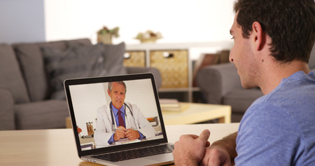 Guy using laptop to talk to doctor Stok Fotoğraf
