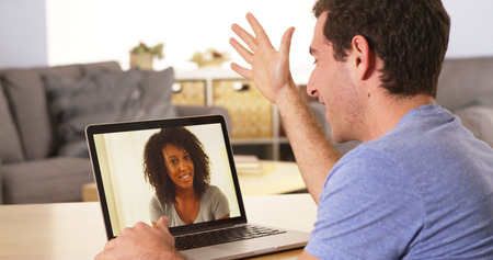 Multi-ethnic friends webcamming on laptop