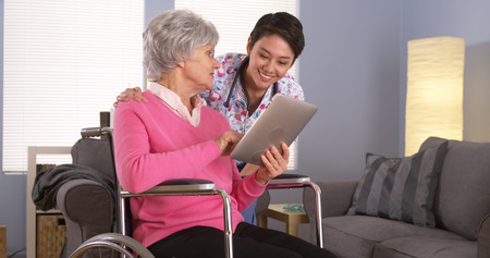 home health care: Chinese woman and Elderly patient talking with tablet