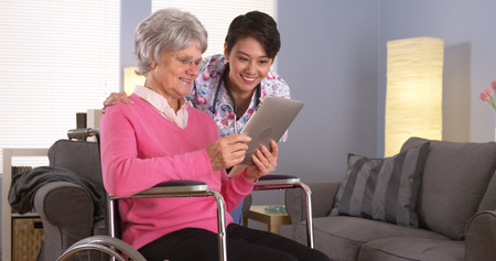 Elderly patient and Asian nurse talking with tablet photo