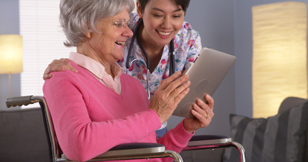 Elderly patient and Asian nurse having fun with tablet Stock Photo
