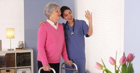 Happy elderly woman patient talking with Asian nurse photo
