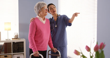 Chinese nurse and elderly woman patient looking out window photo