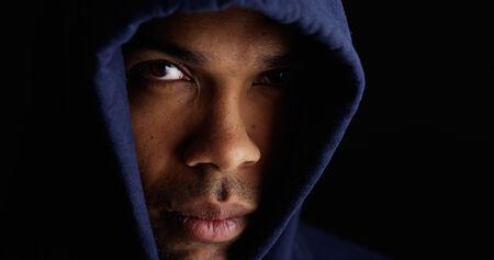 looking down: Black man wearing blue sweater Stock Photo