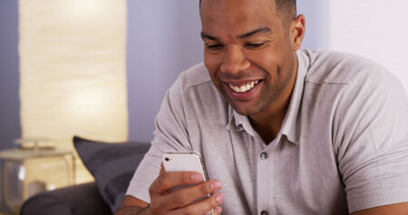 mobile voip: Black man webcamming with mother on smartphone