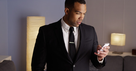 Handsome black businessman typing on smartphone photo