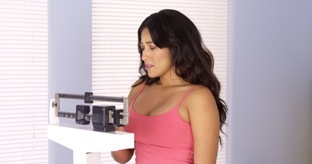 Hispanic woman sad after checking her weight on scale