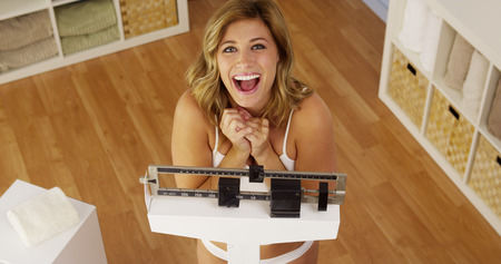 weighing: Healthy young woman weighing herself on scale