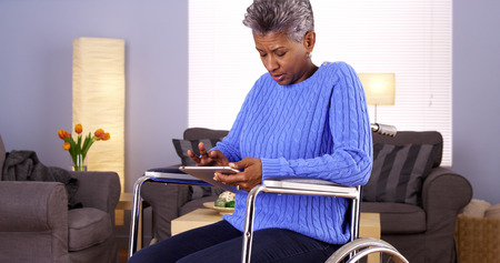 handicapped: Mature African woman sitting in wheelchair with tablet Stock Photo