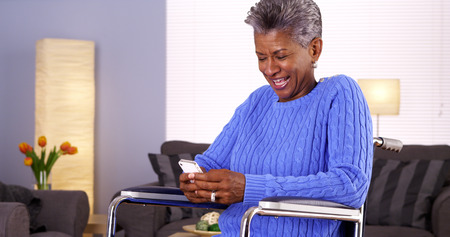 Mature black woman texting on smartphone Фото со стока