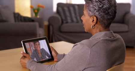 Mature African woman talking with granddaughter on tablet photo
