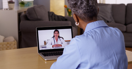 chat: Doctor talking to Senior African woman patient over webcam Stock Photo