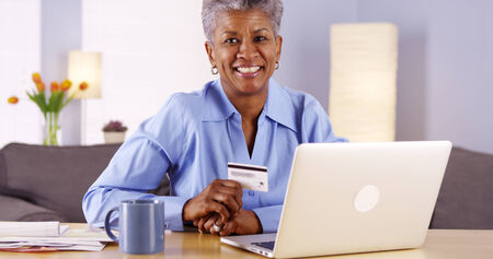 managing money: Happy Mature African woman approved with new credit card