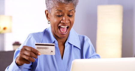 purchase: Happy Mature African woman buying things online Stock Photo