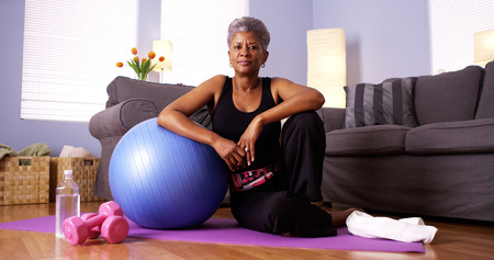 Senior Black woman sitting on floor with exercise equipment Stock Photo