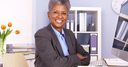 Black businesswoman sitting at desk smiling