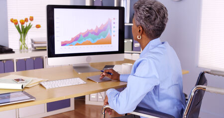 Handicapped African businesswoman working at desk photo