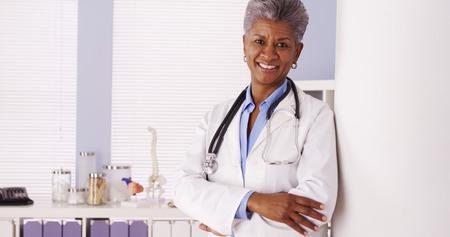 Happy Black Senior doctor standing in office