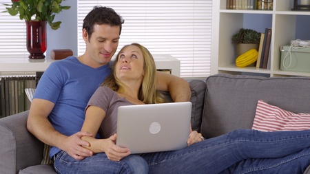 sweet couple: Sweet couple sitting on couch with laptop
