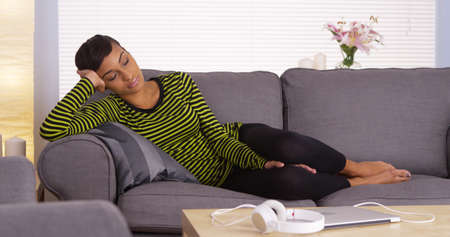 undisturbed: Attractive African woman sleeping on couch Stock Photo