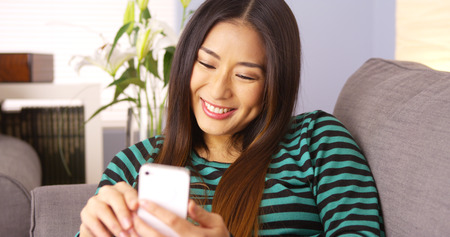 Japanese woman using smartphone on couch