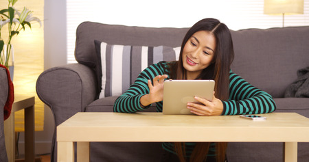 Japanese woman using tablet on coffee table