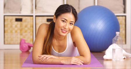 looking after: Happy Japanese woman lying on yoga matt
