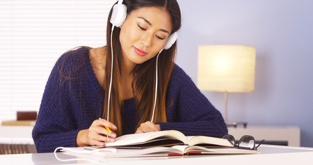 Chinese woman listening to music while doing homework photo